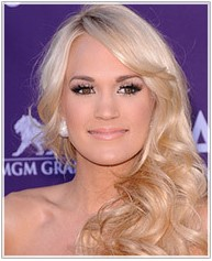 Carrie Underwood's hight forehead hairstyle is a long wavy style with side swept bangs to distratc form high forehead