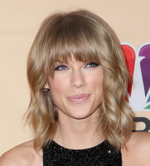 Taylor Swift with full fringe medium length hairstyle