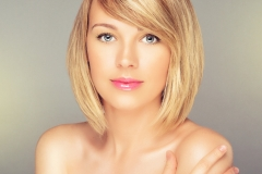 Beautiful Blonde Woman with Blonde Bob Hairstyle and side swept bangs.